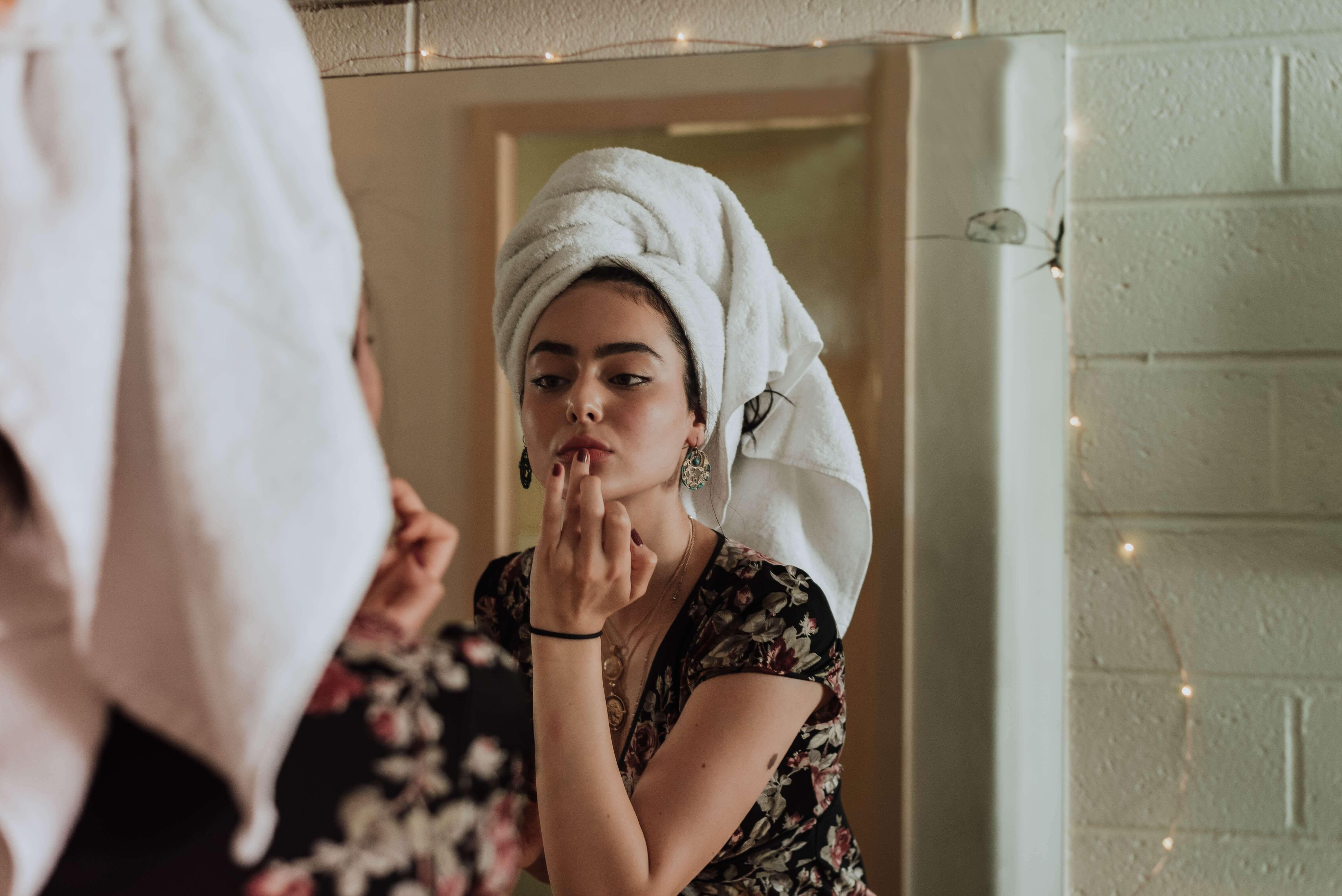 femme devant un miroir qui se maquille